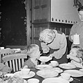 Kinderen eten aan een tafel Jongetje wordt gevoerd door oudere vrouw, Bestanddeelnr 255-9472.jpg