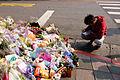 Kneeling Man Writting Pray Card at Liu Murder Place 20160330.jpg