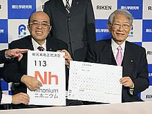 "Lead researcher Kosuke Morita and Riken president Hiroshi Matsumoto from Riken showing ""Nh"" being added to the periodic table"