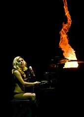 Right profile of a blond woman in a black leotard sitting in front of a piano. Her left leg is on her right one and her face is partially obscured by her wavy hair