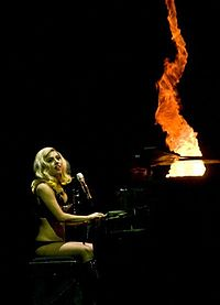 Right profile of a blond woman in a black leotard sitting in front of a piano. Her left leg is on her right one and her face is partially obscured by her wavy hair.