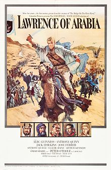 "A painting occupies about 3/4 of the frame. A man riding a galloping horse across sand is the most prominent image. The man is holding a raised scimitar in his right hand; he is wearing a white robe, suggestive of Arabian clothing, but looks to be European with blond hair. Behind him are many more mounted men charging with raised swords, extending far into the background and a sandy hill. At the top of the painting, which shows the sky above the hill, the words ""Lawrence of Arabia"" are written using a large, formal font suggestive of printing. Two lines of small lettering above these words have the phrases ""After five years .... the first motion picture from the creators of 'The Bridge on the River Kwai'"" and ""'Columbia Pictures presents the SAM SPIEGEL - DAVID LEAN production of'"". Beneath the main painting are a row of five small painted portraits of five men wearing Arabian and European dress; one is the same man leading the charge in the main painting. Beneath these paintings is the billing block of the poster: ""starring Alec Guiness - Anthony Quinn / Jack Hawkins - Jose Ferrer / Anthony Quinn - Claude Rains - Arthur Kennedy / with Omar Shariff as 'Ali' - introducing Peter O'Toole as 'Lawrence' / screenplay by Robert Bolt - produced by Sam Speigel - directed by David Lean / Photographed in Super Panavision 70 - a horizon picture in Technicolor""."