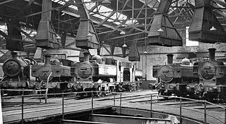 The inside of an engine shed with part of a turntable in the foreground. A number of engines are arranged round the turntable, each with their chimneys under large ventilation cowls.