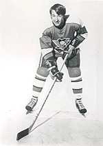 Photograph of Lowell MacDonald holding his hockey stick on the ice