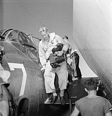 Lt. Charles E. Kerlee, USNR, steps down from the wing of a TBF after photographing the raid on Wake. Using two K-20... - NARA - 520610.jpg