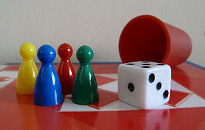 Glossary of board games - Equipment for Ludo: four Ludo pieces, a die, a dice cup, a Ludo board