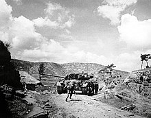 A tank advances up a hill followed by men in military uniform