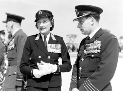 Informal outdoor portrait of man and woman both wearing dark military uniforms with medals and peaked caps