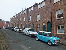 A row of nine identical brick cottages, with a green door and rising sash window on the ground floor, and a single rising sash window on the first floor. Above, built into the roof is a wide window, twelve panes long and four panes high. The cottages are built directly on the street, in front of one is a turquoise and white T registered Mini.