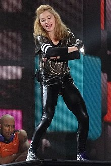 Madonna in tight black spandex and a glittering shirt, with gloves on her hand and elbow, poses on stage.
