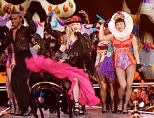 The Peoples Republic of 69 and her dancers in colorful cloths dancing onstage