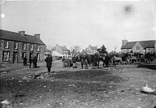 monochrome view of carts and people with houses and church beyond