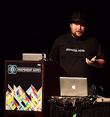 Notch speaking at GDC 2011, in front of a computer and wearing a fedora.