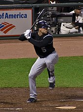 A man in a black baseball jersey and pinstriped baseball pants stands at home plate. He is batting right-handed, holding a black baseball bat over his right shoulder. He is wearing white baseball gloves and a black batting helmet.