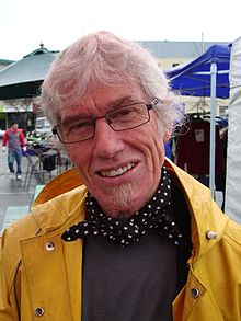 Portrait photo of a man in his late 60s with grey hair and glasses in a raincoat
