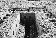 A rubble-strewn rectangular concrete opening with a long thin slot in the middle. More rubble can be seen at the bottom of the shaft in the bottom centre of the photograph