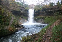 Minnehaha Falls surrounded by dirt and green foliage probably in early spring