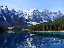 Photographie du lac Moraine, avec, en arrière-plan, les montagnes d'Alberta, et les neiges éternelles qui couvrent leur sommet