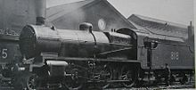 Side-and-front view of a modified version of the N class on shed. The distinguishing feature from normal N class locomotives is the tall cylindrical chimney on the smokebox. A member of the crew is standing next to the tender.