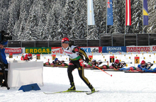 A woman on cross country skies wearing a red cap, a white jersey with the number 15 and black trousers skies away from a shooting range covered in snow. Half a dozen people in the background are shooting while lying on the ground.
