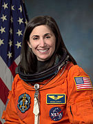 A female Caucasian astronaut wearing her orange mission suit with the American flag embroidered on her shoulder, and name tag and mission patches embroidered on her chest.
