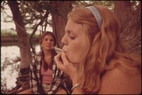 ONE GIRL SMOKES POT WHILE HER FRIEND WATCHES DURING AN OUTING IN CEDAR WOODS NEAR LEAKEY, TEXAS. (TAKEN WITH... - NARA - 554906.tif