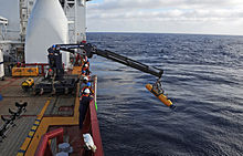 Crane lowering the torpedo-shaped Bluefin 21 into the water off the side of the Ocean Shield.