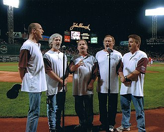 "Orleans (band) - Orleans, singing the national anthem at Fenway Park in July 2006. Left to right: Charlie Morgan, Lance Hoppen, Larry Hoppen, Dennis ""Fly"" Amero, Lane Hoppen."