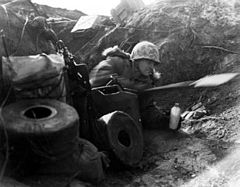 A Caucasian soldier wearing a camouflage helmet and thick winter clothing lies on his side in a trench facing the right of the photo, holding a canteen in his left hand and using an entrenching tool with his right hand. The soldier is surrounded by rolls of communication line, jerries and boxes of equipment. Behind him, the skyline can be seen above the top of the earth works.