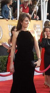 In the center of the photo, a Hispanic women wearing a long sleeveless black dress with light brown hair is shown. Men and women, as well as a red carpet that is roped-off and a green bush can be seen.