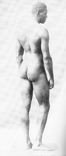 a naked white man standing with his back to the camera and his face in profile