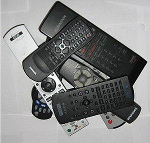A series of remotes piled on top and alongside...