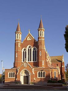 A front facing view of Portsmouth's Roman Catholic cathedral, St John the Evangelist. The cathedral itself is made of brick and has a large chancel and nave at the front. Stained windows are also seen above the front door.
