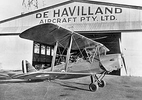 "Biplane on tarmac in front of hanger marked ""De Havilland Aircraft Pty Ltd"""