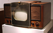 The RCA 630-TS, the first mass-produced television set, which sold in 1946–1947.  Large wood casing with speakers on either side of a small screen in the middle of the unit.  Knobs located on the left and right of the front part of the TV.