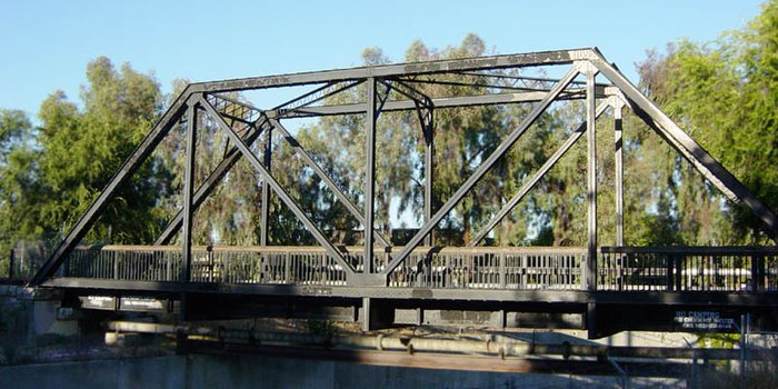 Truss bridge for a single-track railway, converted to pedestrian use and pipeline support. In this example the truss is the assembly of triangular units supporting the bridge. RRTrussBridgeSideView.jpg