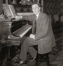 Black and white photograph of a thin, clean-shaven man seated at a piano