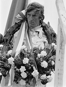 Photograph of Jochen Rindt on a winner's rostrum with a laurel wreath around his neck