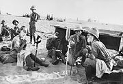 Four men, two wearing pith helmets, sit in the sand, shaving. Three have soap on their faces.