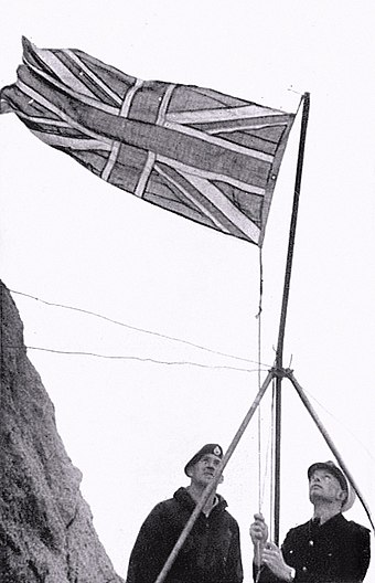Lieutenant Commander Desmond Scott hoists the Union Flag in 1955 Rockall Union flag hoisted 1955.jpg