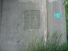 A concrete bridge support with State Highway Route 42 stamped onto it. A green sign seen to the right on the bridge support reads 0114-155 34.69