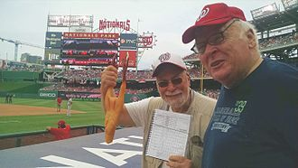 "Washington Nationals - ""Rubber Chicken Man"" Hugh Kaufman cheers on the Washington Nationals with baseball writer Paul Dickson. Kaufman waves a rubber chicken over the Nats' dugout to ward off bad luck, and sometimes ritually ""sacrifices"" them to improve team performance."