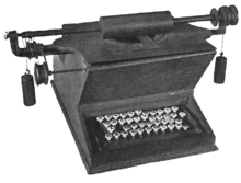 "A wooden typewriter with a ""QWE-TY"" keyboard composed of circular, white keys. The platen rests on top of the device, connected to a bar which extends several inches beyond the sides of the machine. Counterweights are suspended from each end of the bar, to which several wheels and gears are also attached."