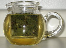 A small clear pot with green oolong tea