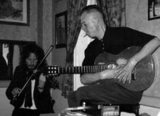 Spontaneous Music Ensemble - The SME playing in Islington, London, 1991. Roger Smith plays guitar and Nigel Coombes plays violin. John Stevens plays drums and cornet out of frame.