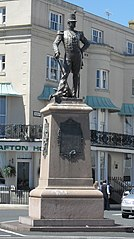 Bronze statue of soldier of Royal Sussex Regiment, in full dress uniform with plumed shako, and with drawn sword; cannon to rear