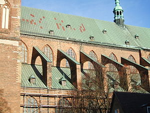 Clerestory - The church of St. Nicolai, Stralsund. The clerestory is the level between the two green roofs, reinforced here by flying buttresses.