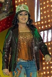 Sunidhi Chauhan performing on stage with a cap on her and wearing a black jacket