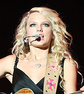 A blonde woman wearing a dark shirt is playing the guitar and singing