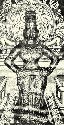 A black-and-white image of an idol of an arms-akimbo bare-chested man, wearing a conical head-gear, a dhoti and ornaments. The idol is placed on a brick, and backed by a decorated halo.